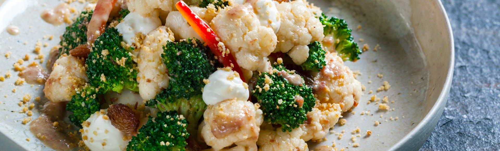 Τραγανό μπρόκολο και κουνουπίδι, μπέικον, σταφίδες, τρίμμα καβουρδισμένου φουντουκιού και κρέμα γιαουρτιού