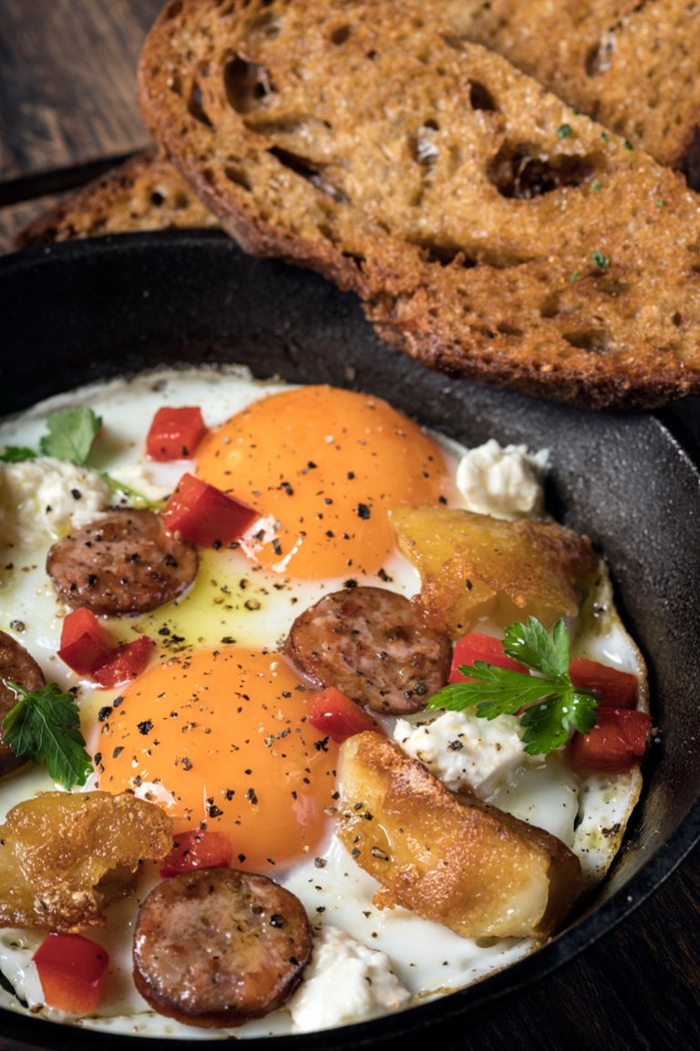 Baked eggs with sausage, feta cheese and peppers