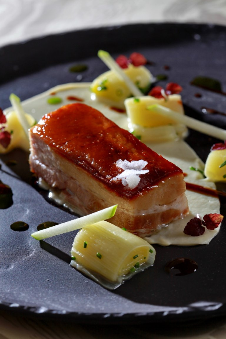 Pork pancetta with braised leek, celeriac puree and coriander sauce