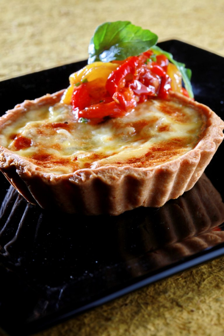 Goat's cheese tart with caramelized onions and roasted peppers salad